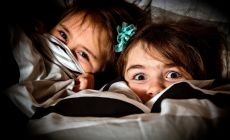girls hiding under the bedcovers - one scared, one smiling