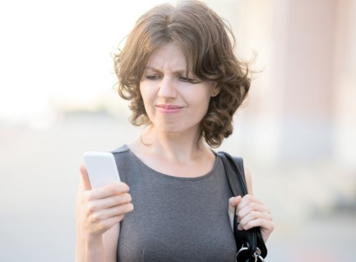 woman looks at phone with unhappy expression
