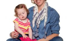 mother with daughter in her lap (child has Down Syndrome)