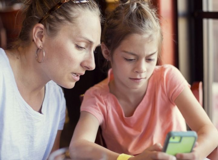mother and tween daughter look at phone
